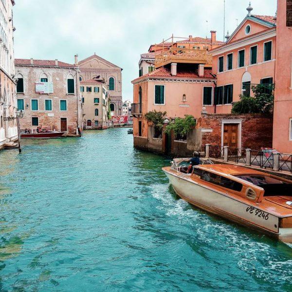 orange-powerboat-between-medium-rise-buildings-208701